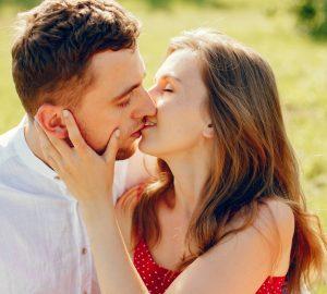 ein liebendes Paar küsst sich auf einer Wiese