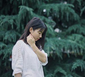 eine nachdenkliche Frau, die nach unten schaut, während sie in der Nähe von Bäumen steht