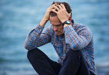 Ein unglücklicher Mann berührte seinen Kopf, während er auf dem Boden saß