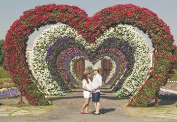 ein Paar stehend Händchen haltend in herzförmigen Blumen
