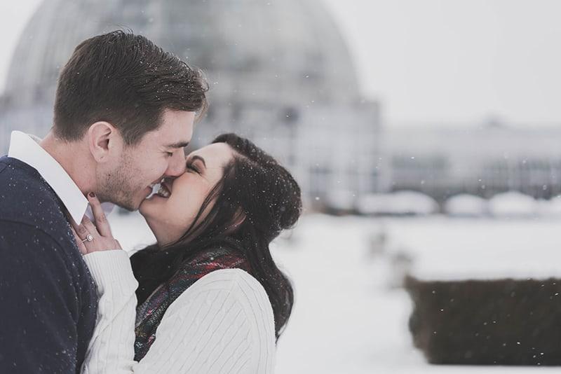 ein glückliches Paar, das sich im Schnee küsst