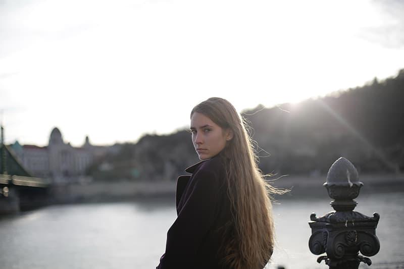 eine Frau mit Ressentiments Gesichtsausdruck in der Nähe des Gewässers stehen