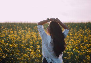 eine Frau, die sich frei fühlt, während sie in der Nähe von gelben Blumen steht