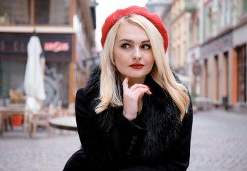 eine Frau mit einer roten Mütze, die ihr Kinn berührt, während sie zur Seite schaut