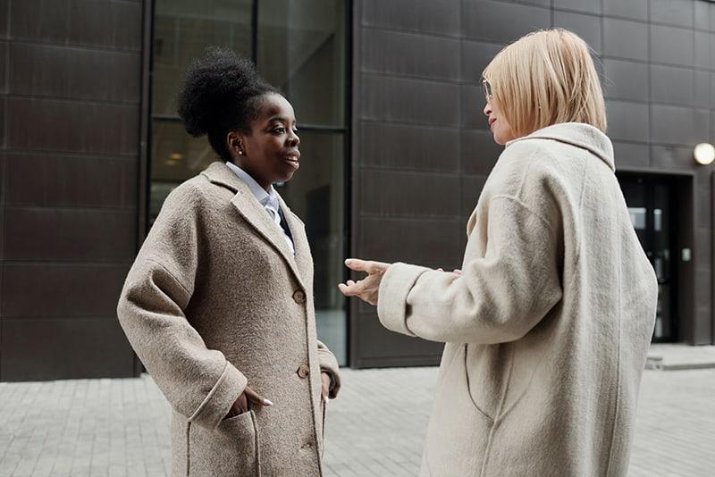 Zwei Frauen unterhalten sich draußen, während sie vor dem Gebäude stehen