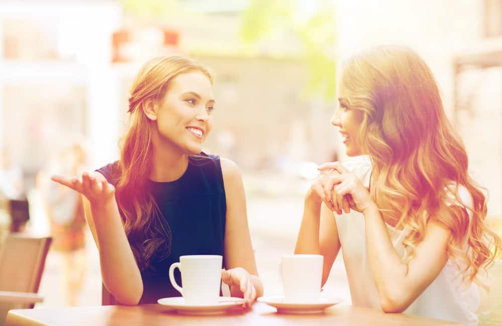 Zwei lächelnde Freunde sitzen und reden beim Kaffee