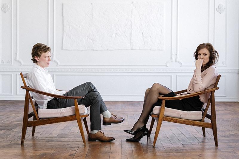 Ein Mann und eine Frau unterhalten sich, während beide sich unwohl fühlen