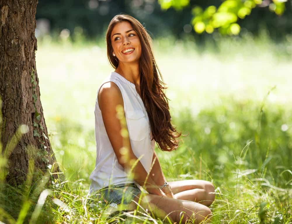 attraktive Brünette, die im Schatten auf dem Gras ruht