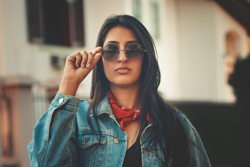 attraktive Brünette mit Sonnenbrille und rotem Schal um den Hals