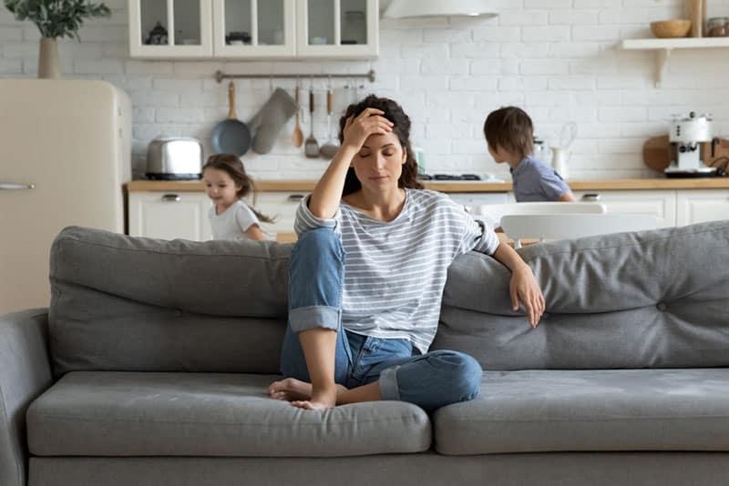 besorgte Frau, die auf der Couch sitzt, während Kinder laufen
