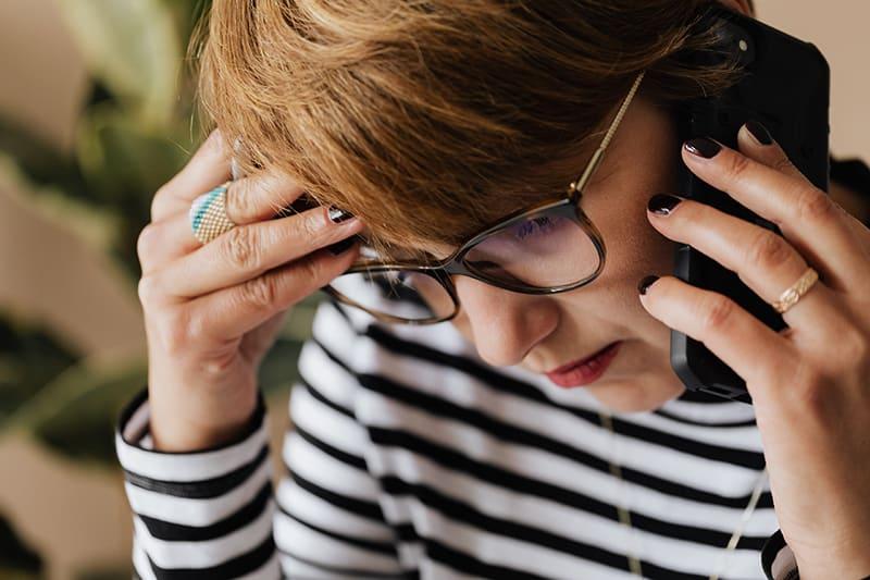 besorgte Frau, die ein Telefongespräch führt und ihren Kopf berührt