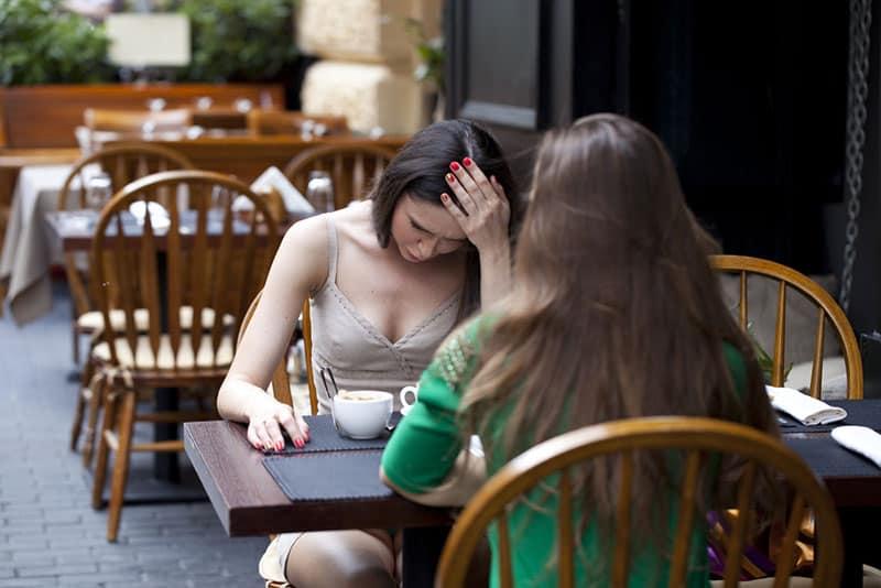 besorgte Frau, die mit Freund auf Kaffee sitzt