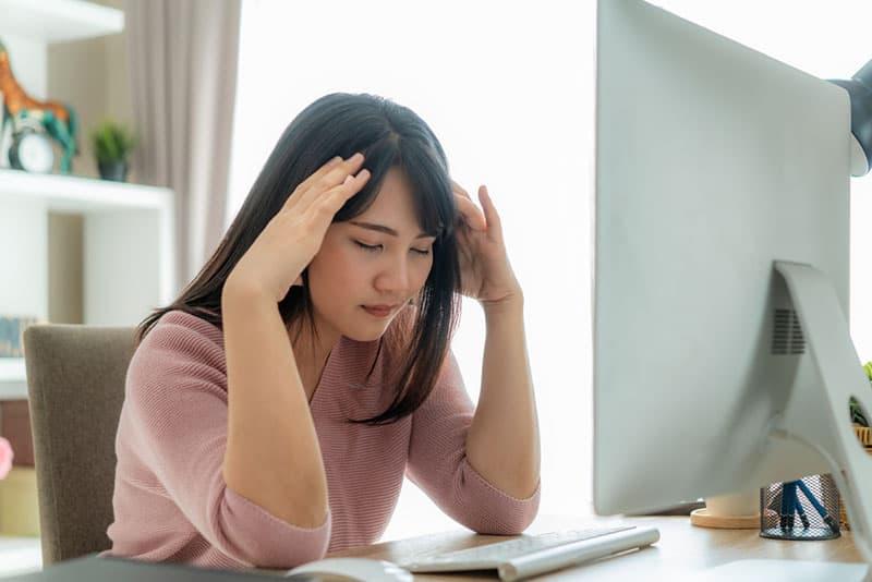 besorgte asiatische Frau, die am Tisch sitzt