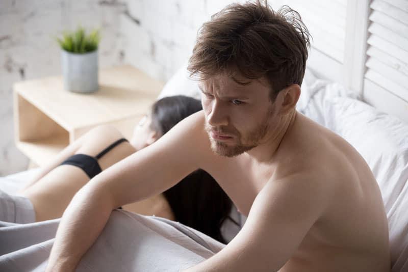 besorgter Mann sitzt im Bett neben seiner Freundin