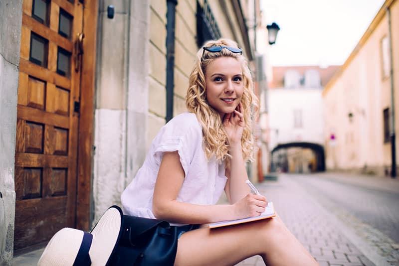 blonde Frau, die draußen sitzt und schreibt