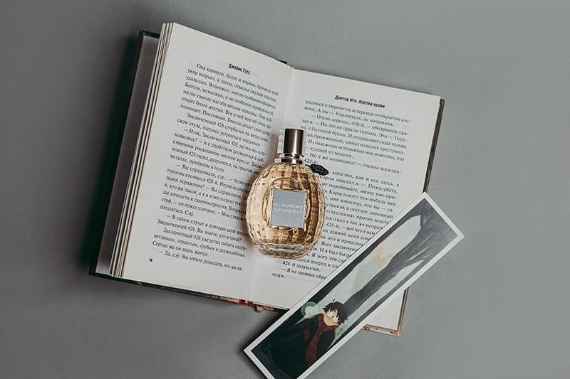das Parfüm einer Frau auf dem geöffneten Buch