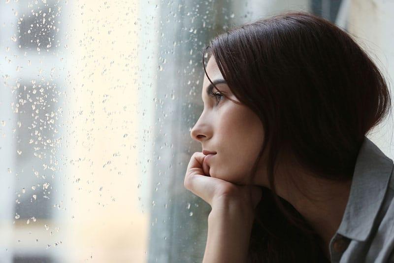 depressive Frau, die durch das regnerische Fenster schaut