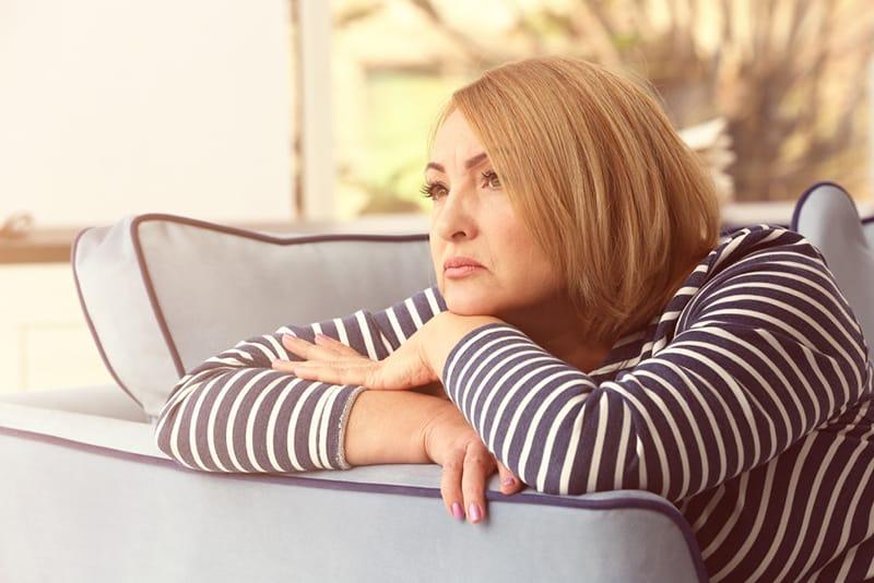 depressive Frau mittleren Alters, die sich auf das Sofa stützt