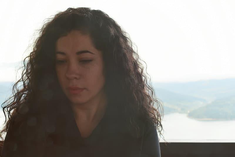 der traurige Blick einer Frau mit schwarzen, üppigen Haaren