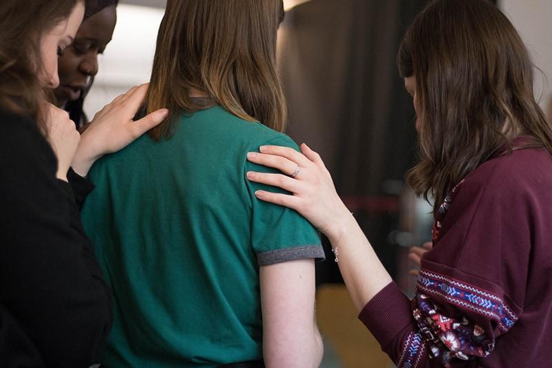 Drei Frauen trösten eine Frau, die ein grünes T-Shirt in einer Selbsthilfegruppensitzung trägt