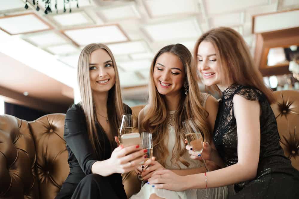 drei lächelnde hübsche Frauen, die Champagner trinken