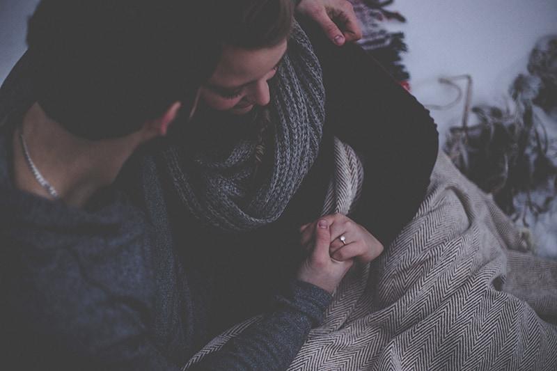 ein Ehepaar, das Hände hält, während es zusammen mit einer Decke bedeckt liegt
