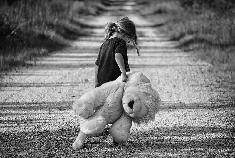 ein Kind, das auf der Straße geht und ein Stofftier hält