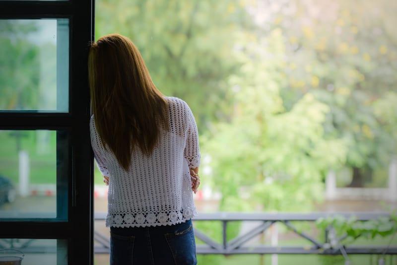 ein Mädchen, das sich gegen einen Schaft am Fenster lehnt