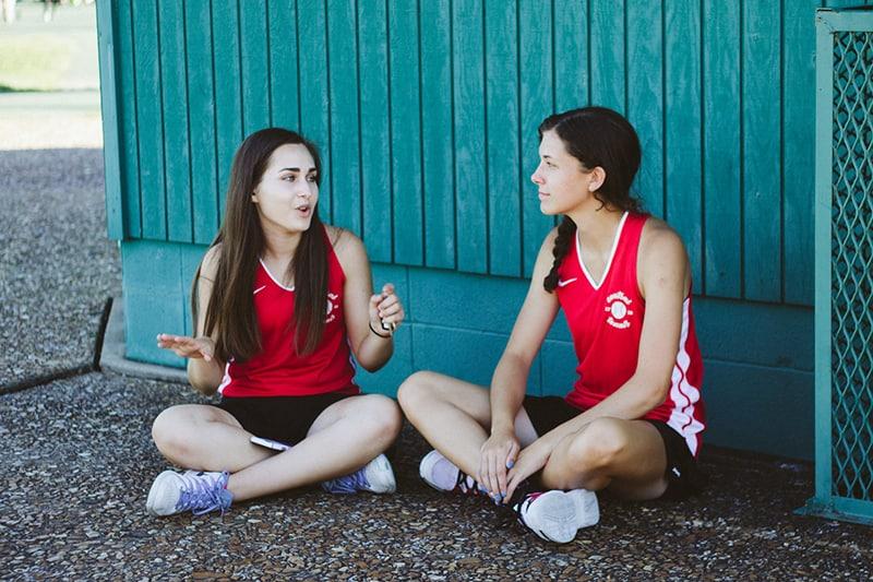 ein Mädchen, das mit ihrer Freundin spricht, während sie auf dem Boden nahe blauer Holzwand sitzt