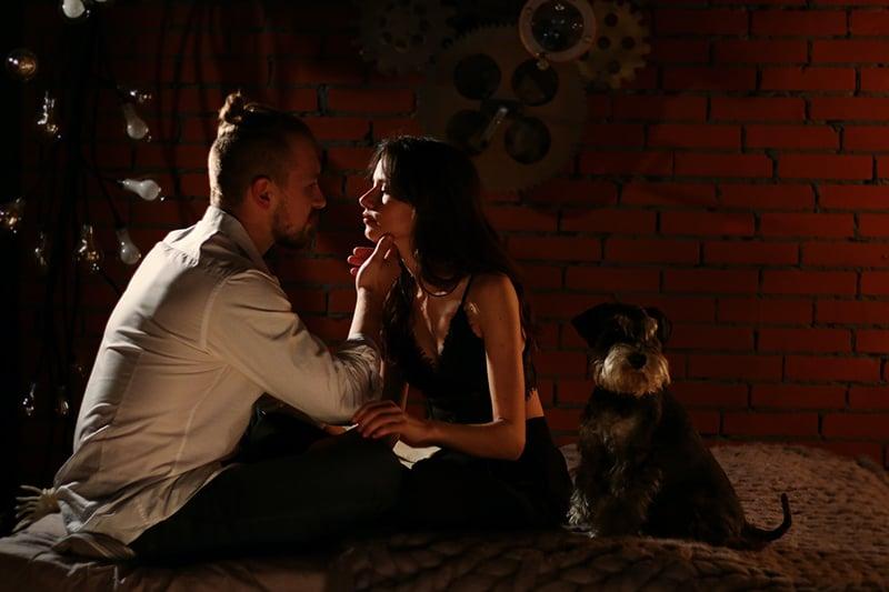 Ein Mann berührt das Gesicht einer Frau, während er auf dem Bett sitzt