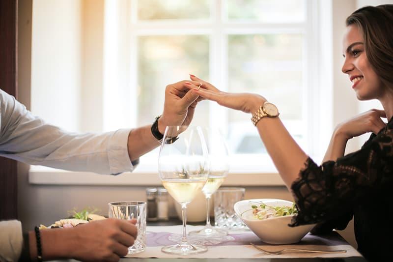 Ein Mann legte einen Ring an die Hand der Frau, während er sie vorschlug