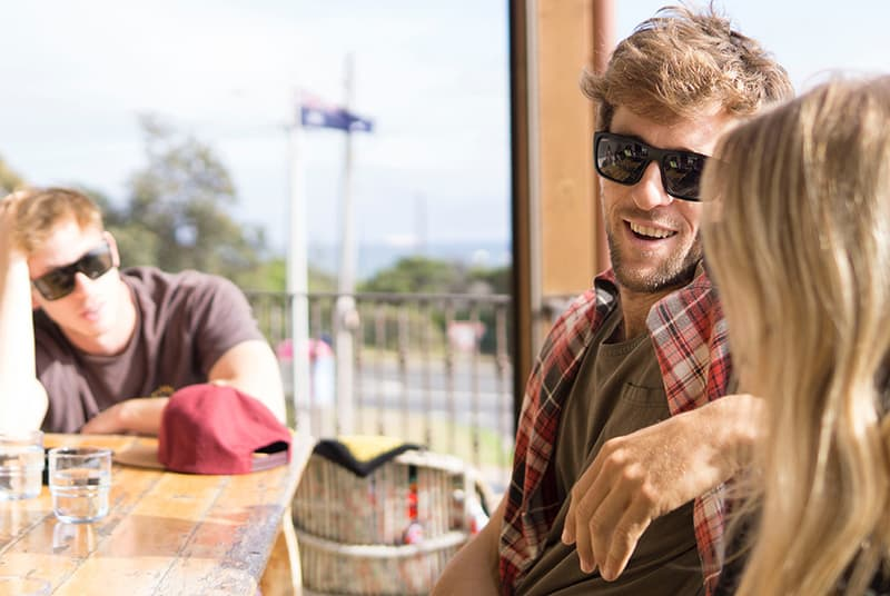 ein Mann, der ein liebendes Paar betrachtet, während er zusammen draußen im Freien am Tisch sitzt