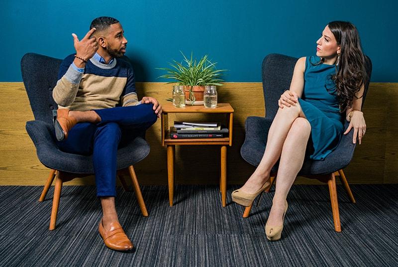 Ein Mann beleidigt eine Frau während eines Gesprächs, während beide in den Sesseln sitzen