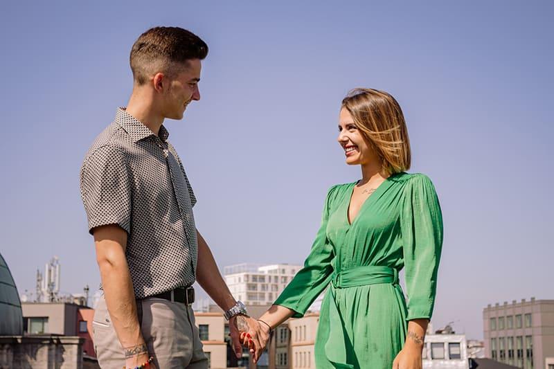 ein Mann, der eine Frau betrachtet, die grünes elegantes Kleid trägt, während Hände hält