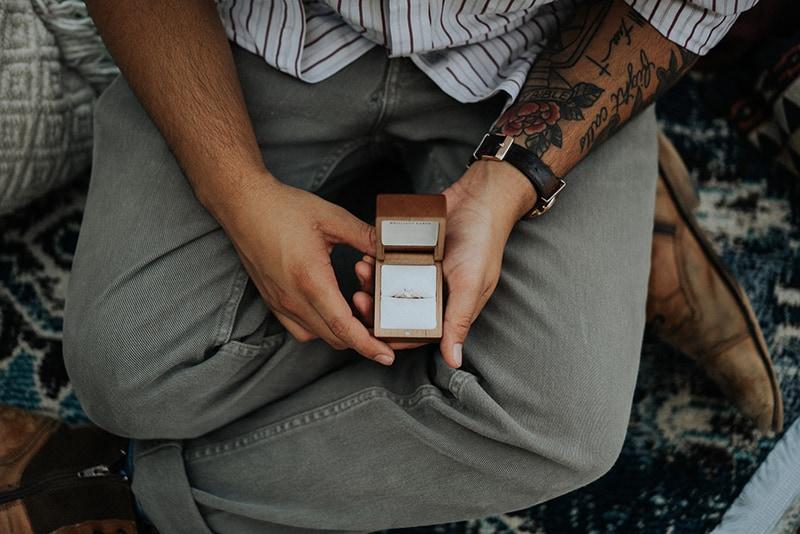 Ein Mann hält eine Schachtel mit einem Ring, während er auf dem Sofa sitzt
