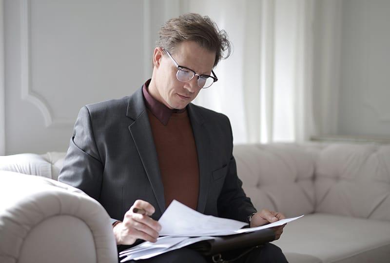Ein Mann liest eine Scheidungsklage, während er auf der Couch sitzt