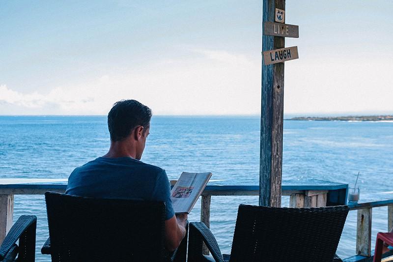 Ein Mann liest eine Zeitschrift, während er sich alleine in der Nähe des Gewässers entspannt