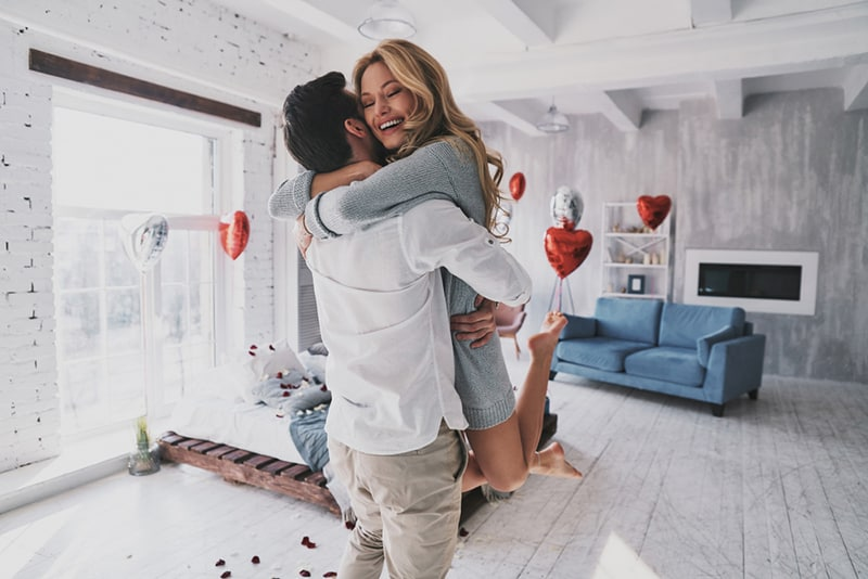 ein Mann, der eine glückliche Frau anhebt, während er im Schlafzimmer steht