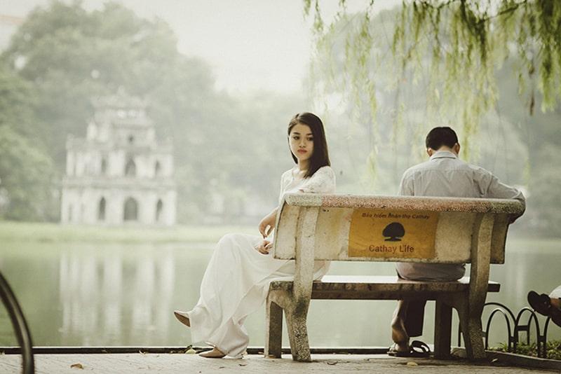 Ein Mann ignoriert eine traurige Frau, während beide auf der Bank sitzen