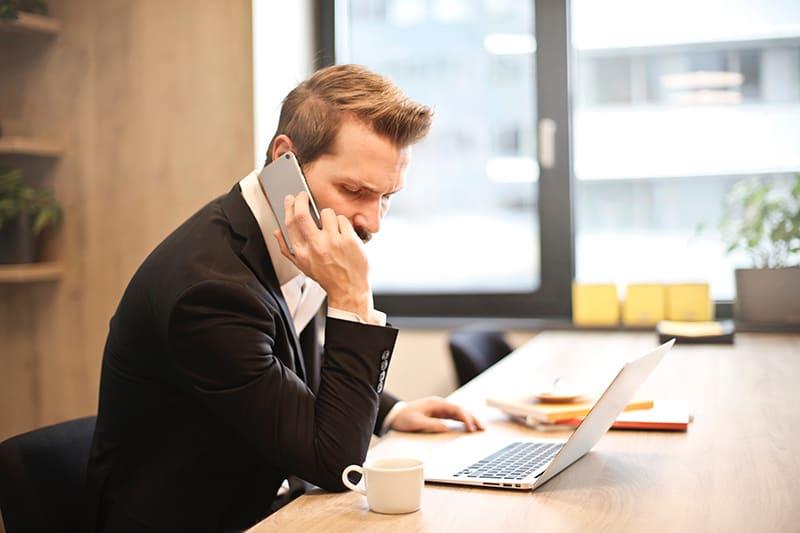 Ein Mann, der einen Anruf hat, während er im Büro vor dem Laptop sitzt