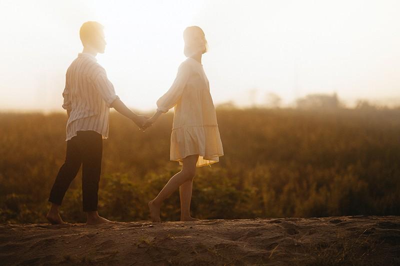 Ein Mann geht einer Frau im Sand nach, die sich an den Händen hält