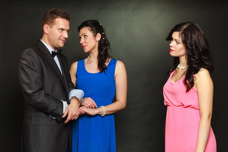 Ein Mann, der mit einer Frau Händchen hält und eine andere Frau im Stehen ansieht