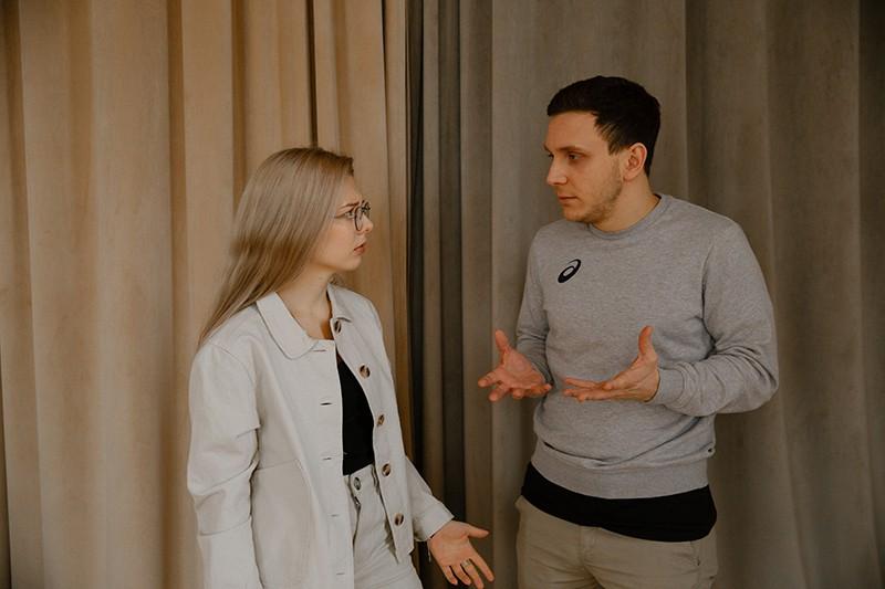 Ein Mann, der verärgert aussieht und mit einer Frau argumentiert, während er zusammen in der Nähe eines beigen Vorhangs steht