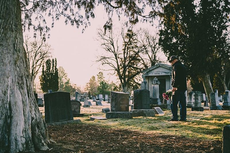 Ein Mann, der vor einem Grab steht und Blumen in der Hand hält