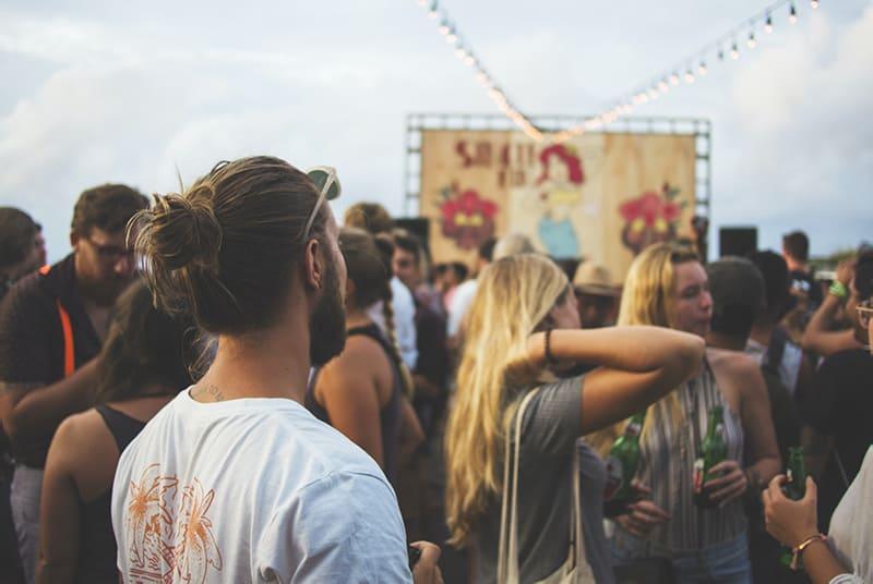 ein Mann, der zwei Frauen auf der Party im Freien betrachtet