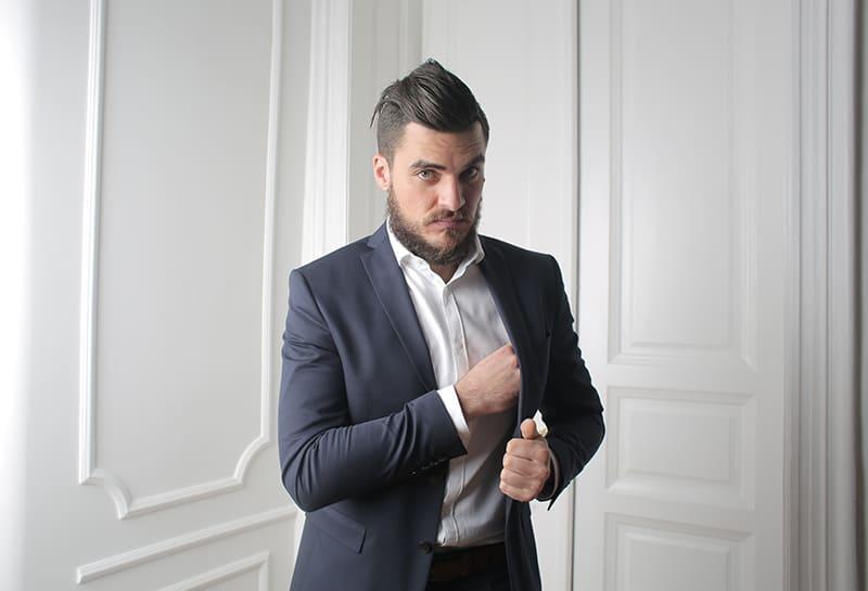 Ein Mann in einem Anzug stand in der Nähe von weißen Türen und sah auf