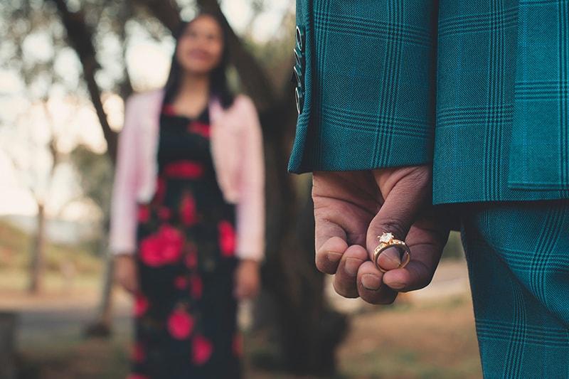 Ein Mann hält einen Diamantring hinter dem Rücken, während eine Frau vor ihm steht