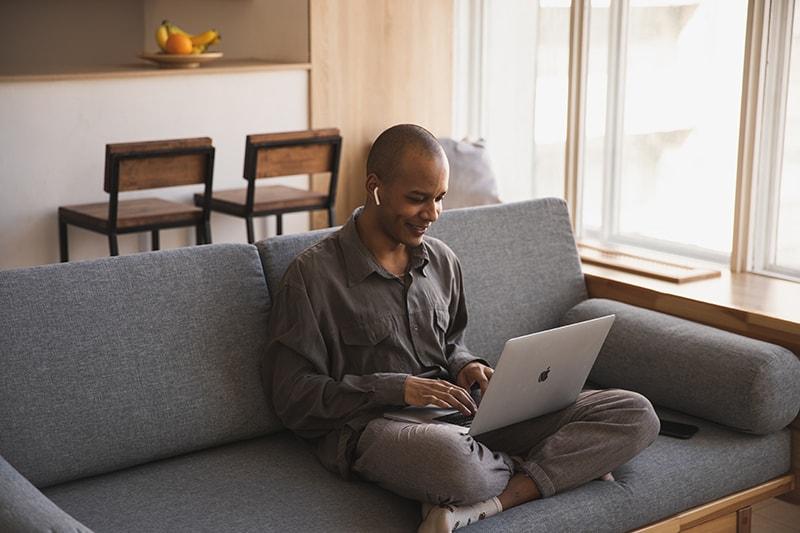 Ein Mann benutzt einen Laptop und plaudert, während er auf der Couch sitzt