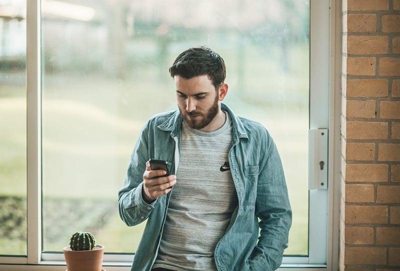 Ein Mann benutzt sein Smartphone, während er in der Nähe des Fensters steht