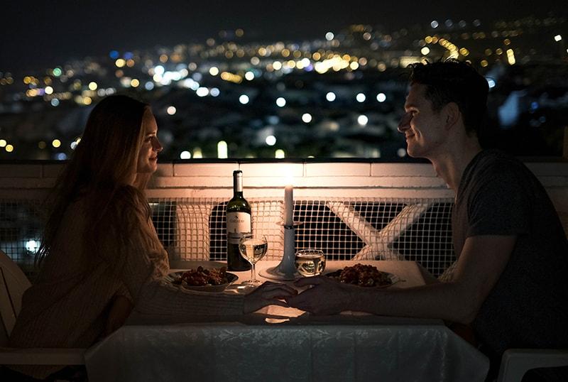 Ein Mann und eine Frau bei einem Date, die Hände halten, während sie am Tisch sitzen